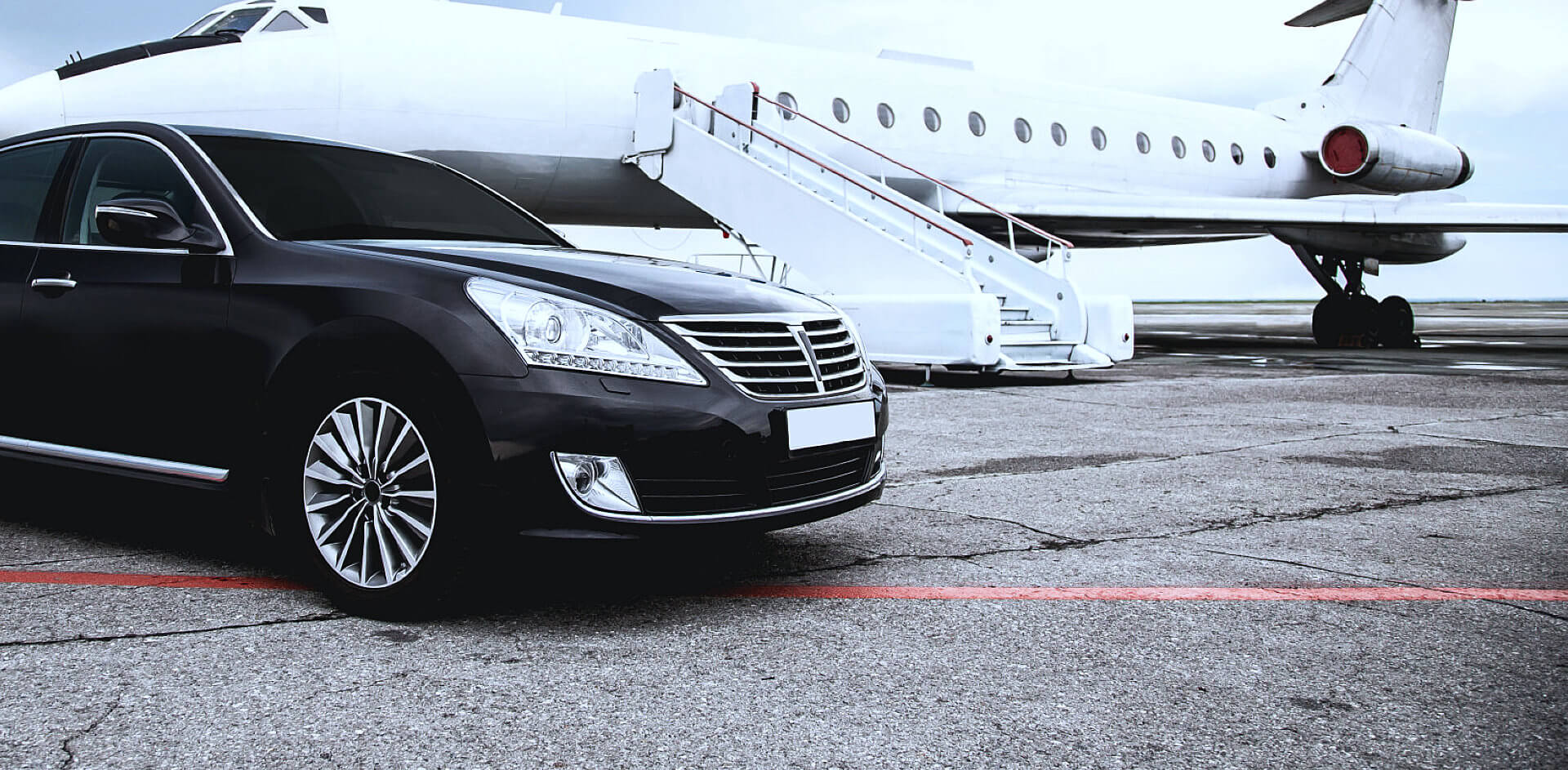 portrait of car with private airplane at the back