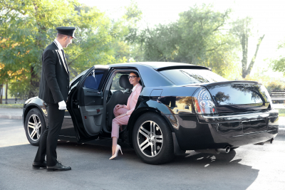 chauffeur opening car door for businesswoman